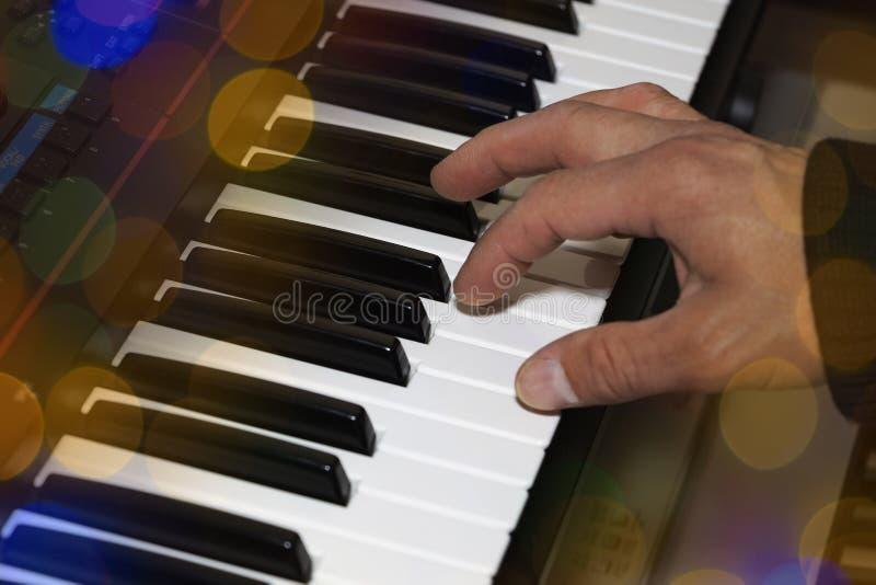 手握钢琴键盘电子琴特写 音乐家的手在钢琴上演奏 库存照片