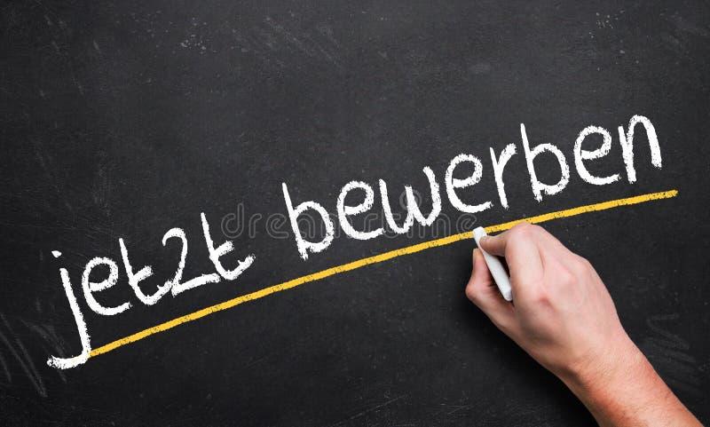 手文字`现在申请! 在一个黑板的`用德语 免版税库存图片