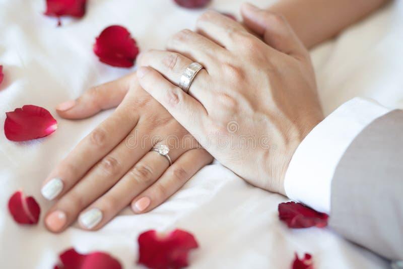 手新郎夫妇恋人的关闭显示戴着在结合在一起使手的新娘的结婚戒指 免版税图库摄影