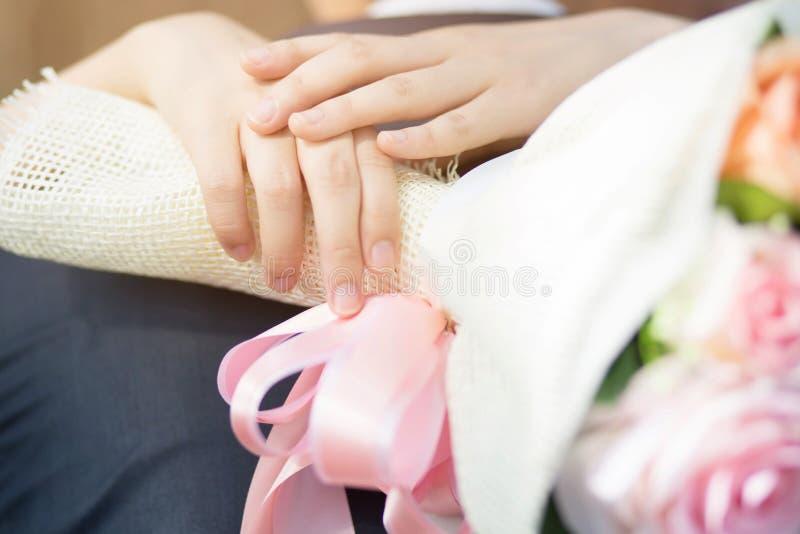 手新郎夫妇恋人的关闭显示戴着在结合在一起使手的新娘的结婚戒指 库存照片