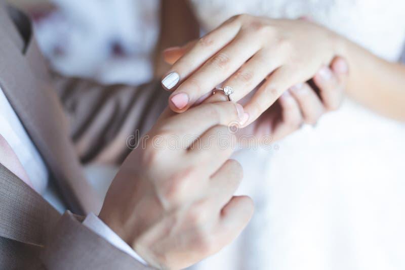 手新郎夫妇的关闭在新娘投入了给结婚戒指 库存图片