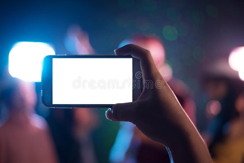 手有空白的白色屏幕的藏品智能手机 照片射击了蓝色 库存图片