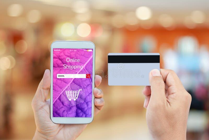 手有网络购物的藏品智能手机在机动性的购物中心背景中和信用卡上弄脏的屏幕 免版税库存图片