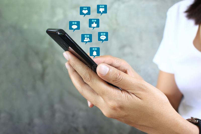手有集合通讯技术和社会媒介全息图或象的藏品智能手机  库存照片