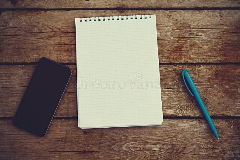 手机、笔记本和笔在老木桌上 库存图片