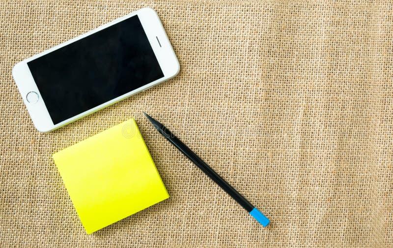手机、笔记薄和铅笔在麻袋布背景 库存图片