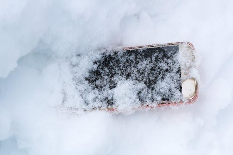 手机偶然地掉下来并且得到了失去在雪 库存照片