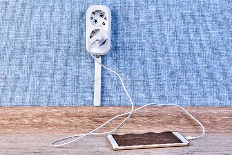 手机充电与壁装电源插座 免版税库存照片