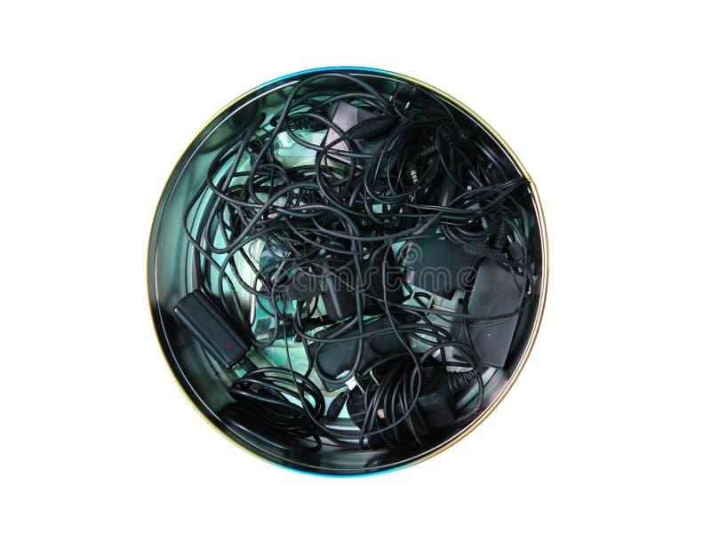 手机充电器杂乱在圆的容器 库存图片