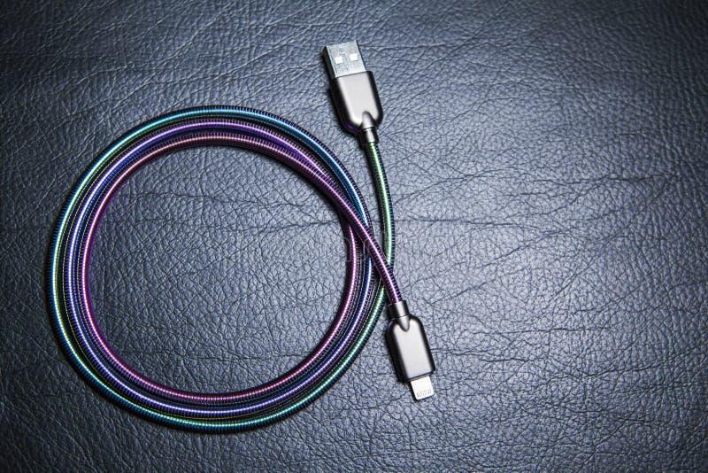 手机充电器缆绳皮革背景 免版税库存照片
