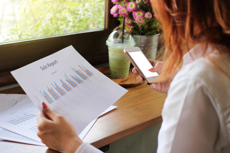 手机后面看法有计算器的app用女商人的人工使用在她的办公室 浅深度的域 免版税库存图片