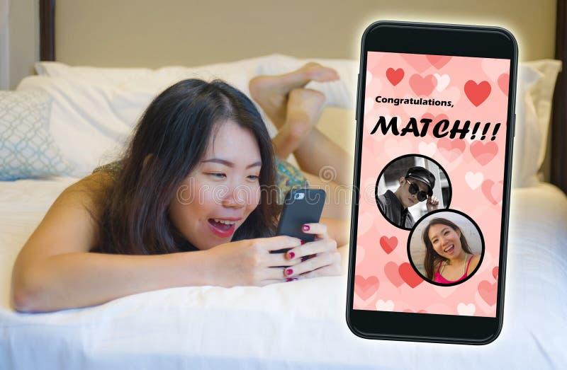 手机和使用网上约会的应用程序的年轻美丽和愉快的亚裔中国女孩快乐接受与英俊的一次比赛 免版税库存照片