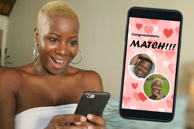 手机和使用网上约会的应用程序的年轻美丽和愉快的黑人美国黑人的妇女激动在与帅哥的比赛 免版税图库摄影