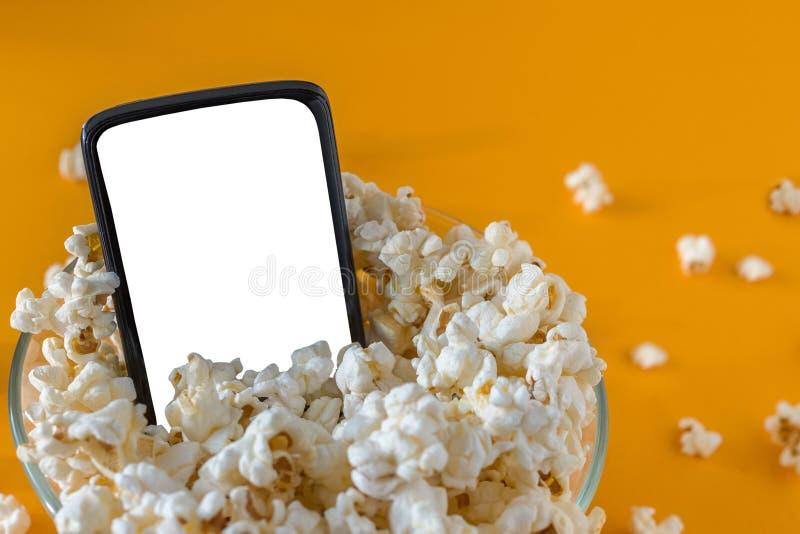 手机和玉米花在一个碗,在一张黄色桌上,特写镜头 概念查出的技术白色 图库摄影