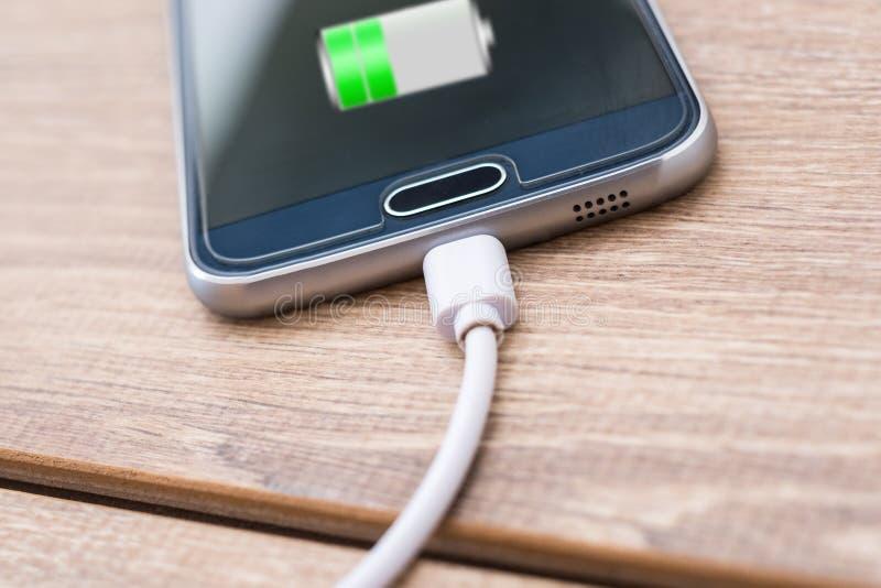 手机和蓄电池充电器在办公桌上缚住 免版税库存照片