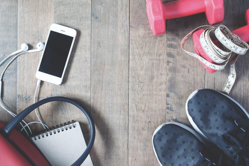 手机和运动器材平的位置在木背景 库存照片