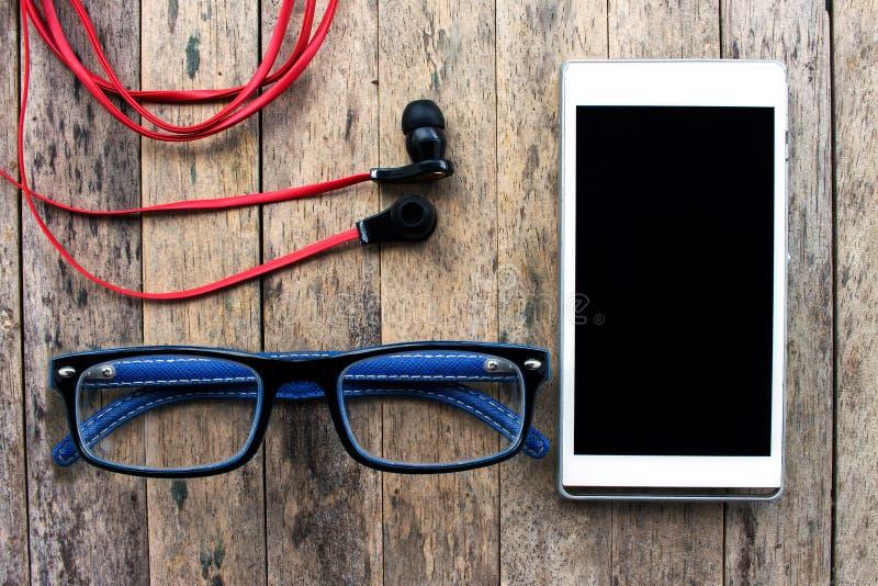 手机和玻璃和耳机在木背景 免版税库存图片