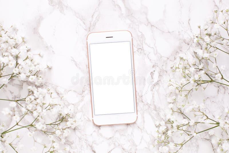 手机嘲笑和在大理石台式视图的白花在平的被放置的样式 ??????? 库存图片