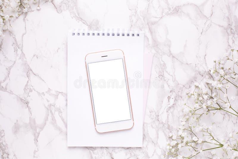 手机嘲笑和在大理石台式视图的白花在平的被放置的样式 ??????? 免版税库存图片
