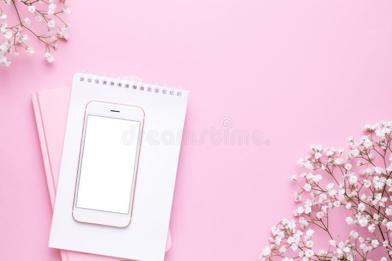 手机嘲笑和在桃红色淡色台式视图的白花在平的被放置的样式 ??????? 库存照片