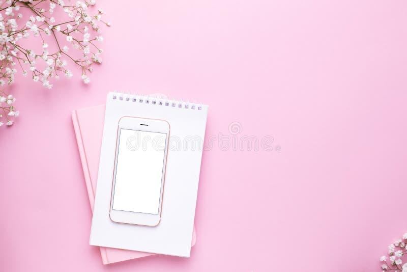 手机嘲笑和在桃红色淡色台式视图的白花在平的被放置的样式 ??????? 免版税库存照片