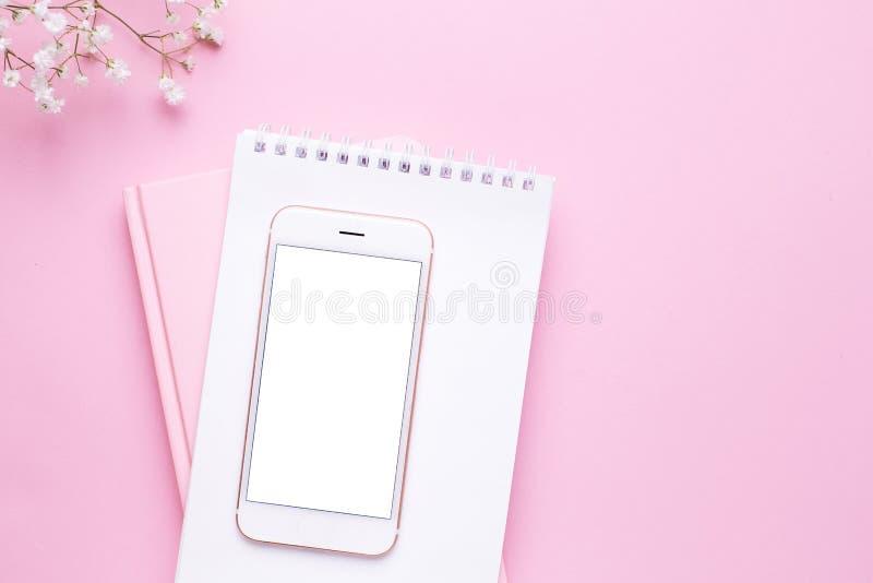 手机嘲笑和在桃红色淡色台式视图的白花在平的被放置的样式 ??????? 图库摄影