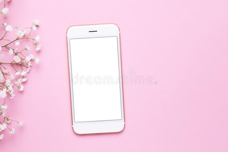 手机嘲笑和在桃红色淡色台式视图的白花在平的被放置的样式 E 库存照片