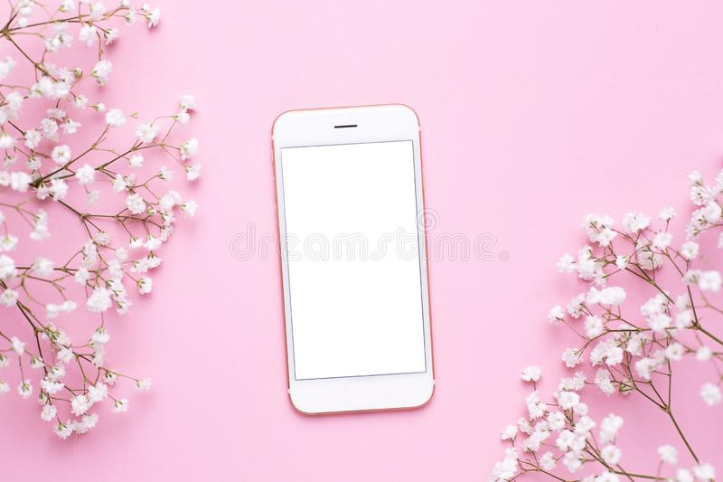 手机嘲笑和在桃红色淡色台式视图的白花在平的被放置的样式 E 免版税图库摄影