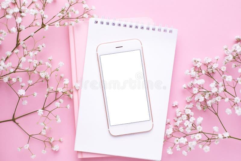 手机嘲笑和在桃红色淡色台式视图的白花在平的被放置的样式 E 库存图片