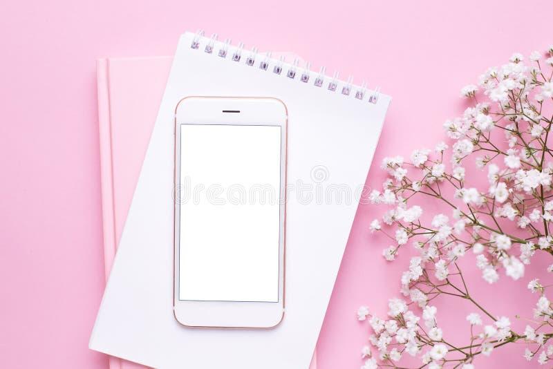 手机嘲笑和在桃红色淡色台式视图的白花在平的被放置的样式 E 免版税库存图片