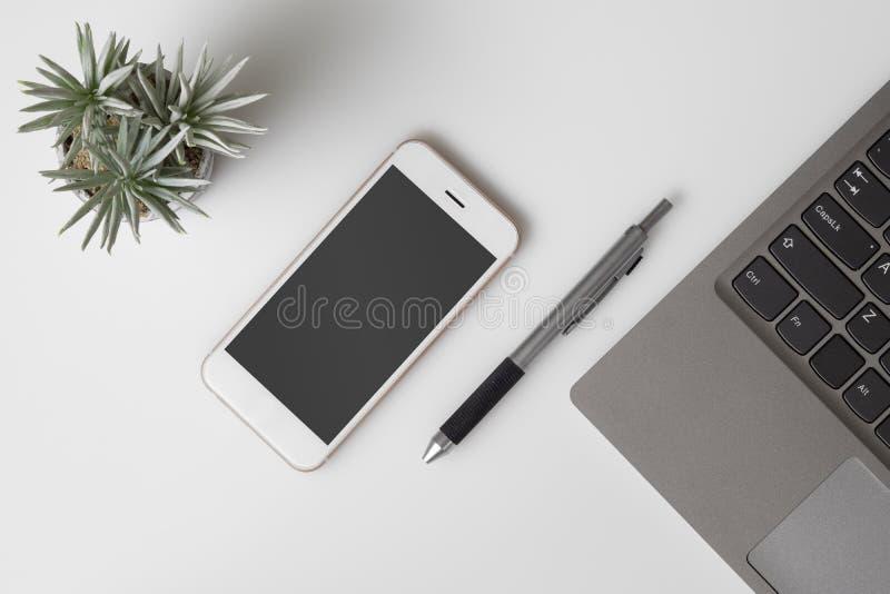 手机大模型,白色办公桌桌顶视图与大模型黑屏智能手机和计算机膝上型计算机的 r 免版税库存图片