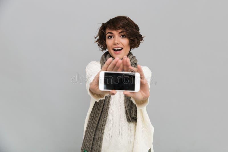 手机惊奇的少妇佩带的围巾陈列显示  免版税图库摄影
