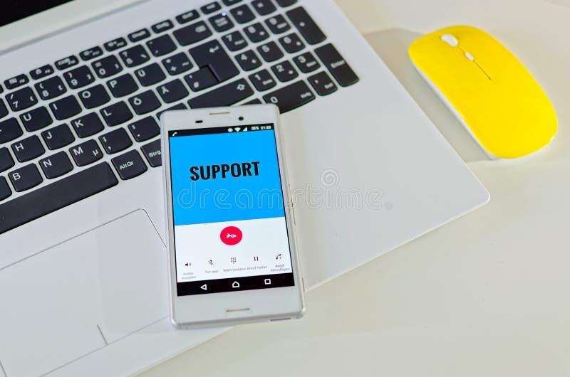 手机有在显示的支持和支持叫,与笔记本,黄色老鼠 库存照片