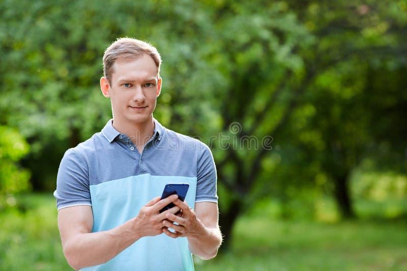 手机照片在人的手上在绿色blured背景 免版税库存图片