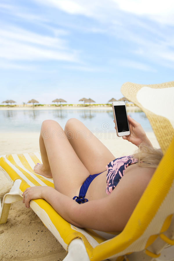 手机的妇女一个热带海滩假期 图库摄影