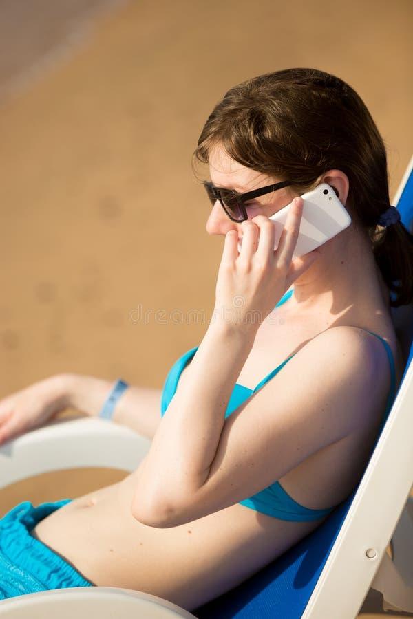 手机的妇女在太阳deckchair 库存图片