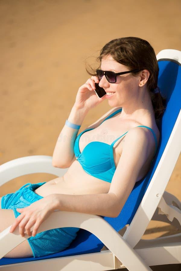 手机的妇女在太阳deckchair 库存照片