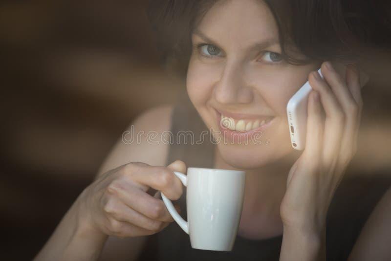 手机的少妇在咖啡馆 库存图片