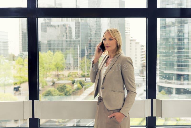 手机的快乐的女商人在现代办公室 免版税库存图片