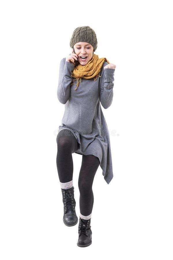 手机的激动的兴奋的年轻时髦的妇女庆祝与紧握拳头的 库存图片