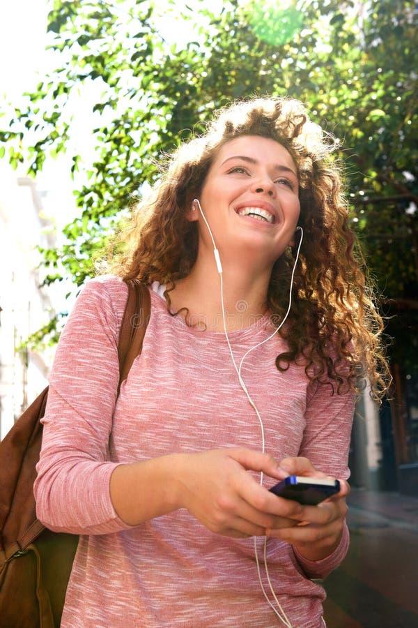 手机的笑的青少年的女孩有外面耳机的 库存图片