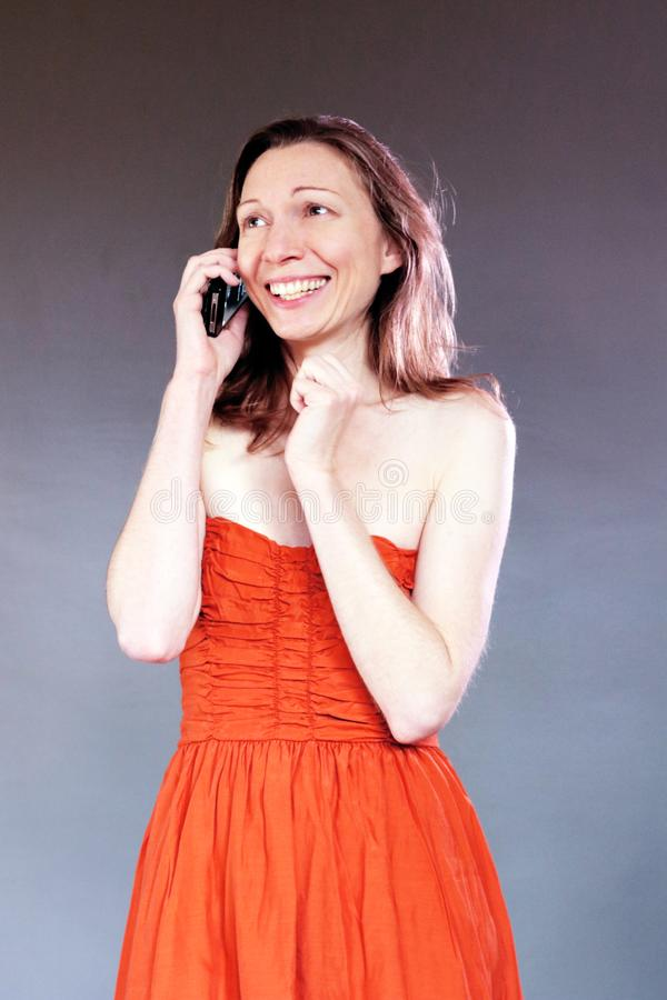 手机笑的聊天的美丽的优等的年轻人的欣快女孩在燕尾服 免版税库存照片