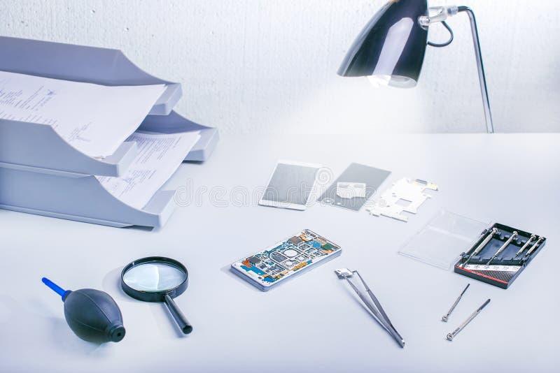 手机零件和修理工具,技术员工作区 专业修理办公室 免版税库存图片
