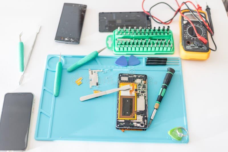 手机零件和修理工具,技术员工作区 免版税库存照片