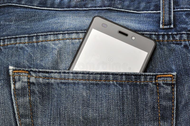 手机,在后面口袋蓝色牛仔裤的手机 免版税图库摄影