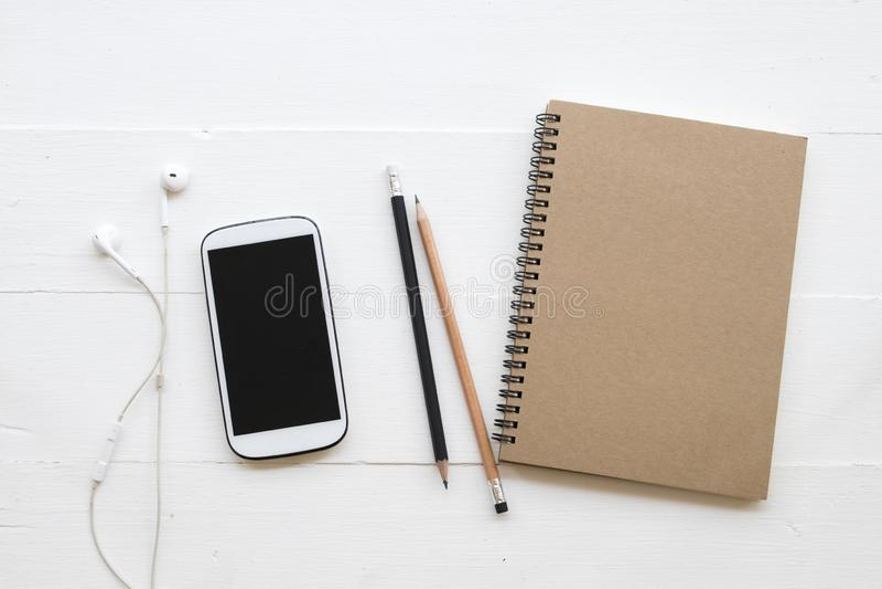 手机,学生研究的文字笔记笔记本  免版税库存照片