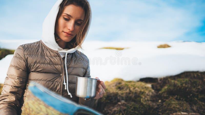手杯子的饮料,在地图的旅游神色,在雪山,行家的人计划的旅行女孩藏品在背景冬天 免版税库存图片