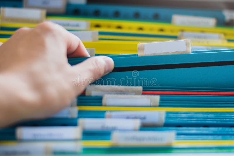 手查寻的特写镜头和选择文件夹从一个小组在架子的文件夹在办公室 库存照片
