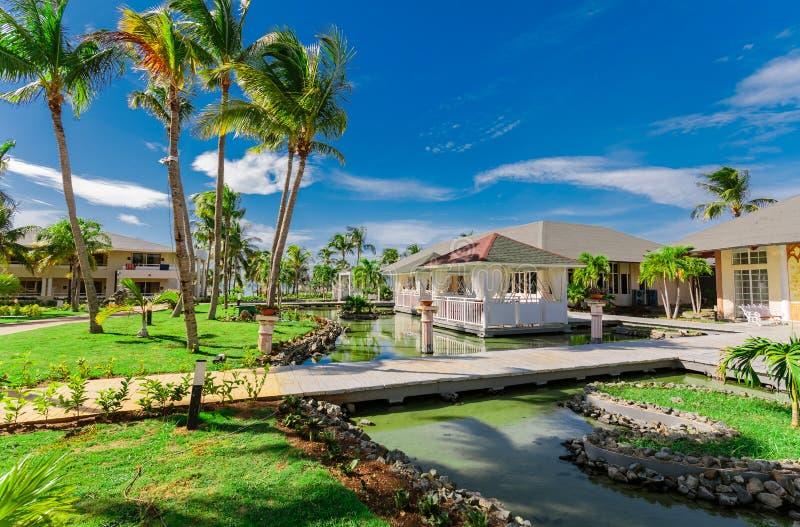 手段地面和餐馆大厦令人惊讶的自然风景视图,在晴朗的gorgeou的水包围的热带庭院里 免版税库存照片