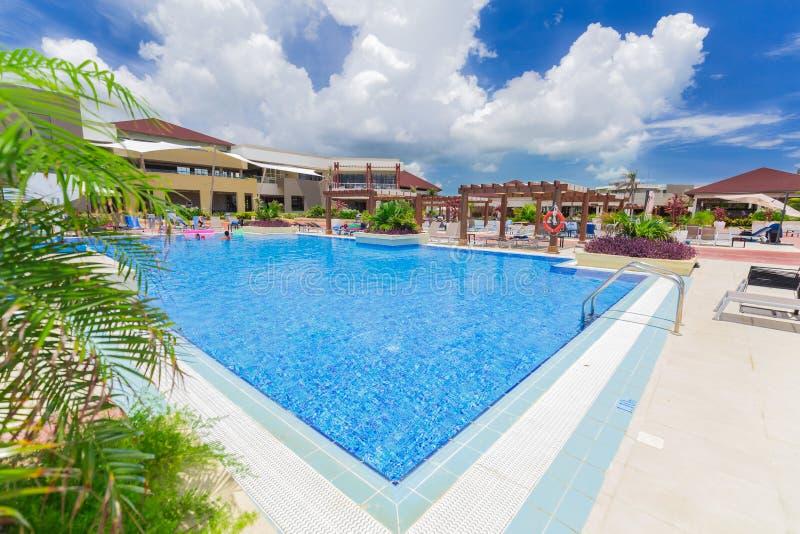 手段室外游泳池和旅馆地面美好的邀请的看法与放松在背景中的人的 免版税库存图片